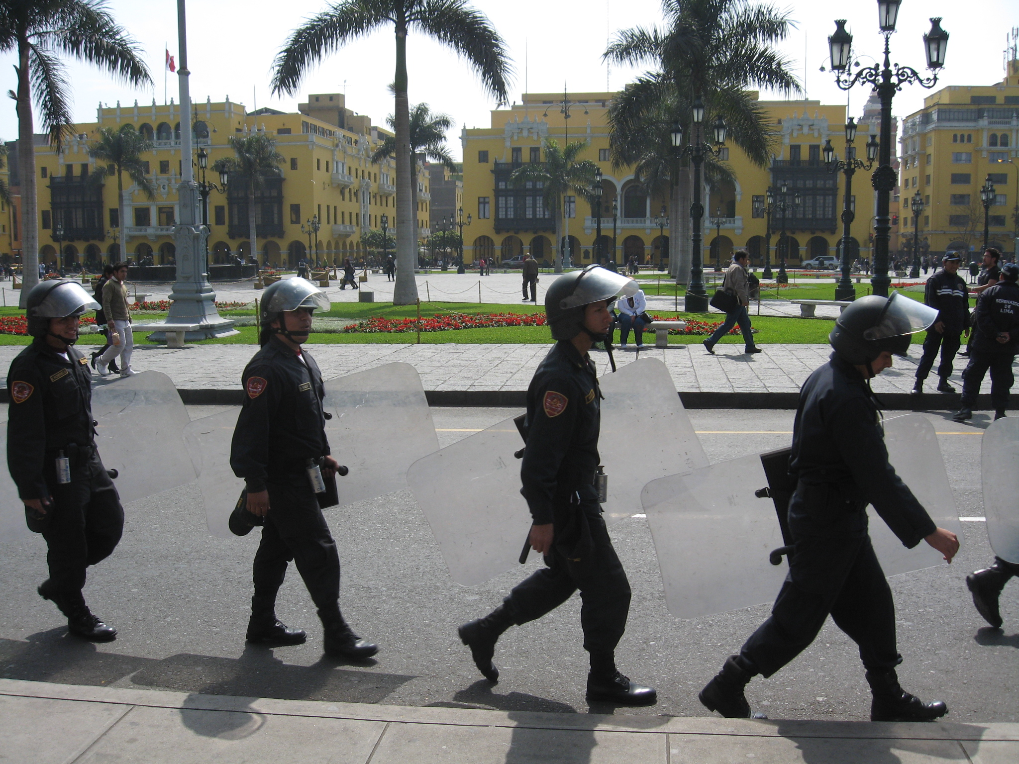 Riot police march on the square in Lima