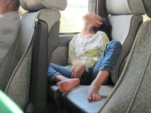 Young Cambodian girl sleeps on a Capitol Tours bus