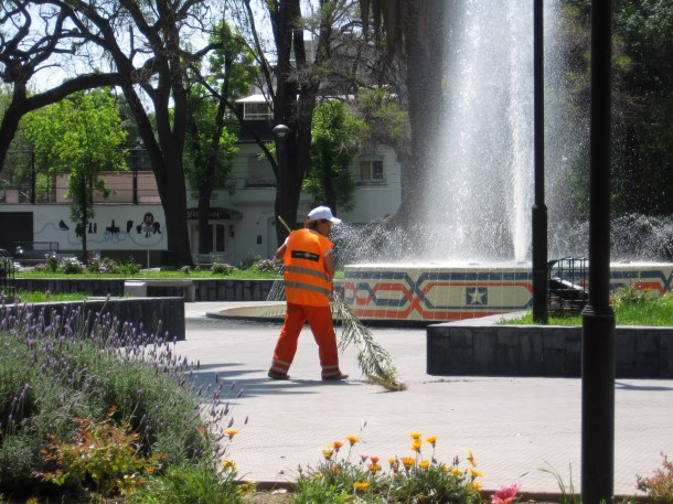 A city worker keeps the plaza clean by sweeping with a palm frond