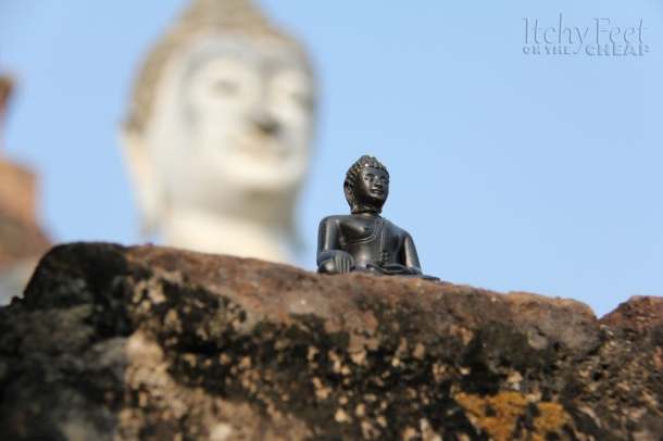 A little Buddha statue sitting in front of a much larger one.